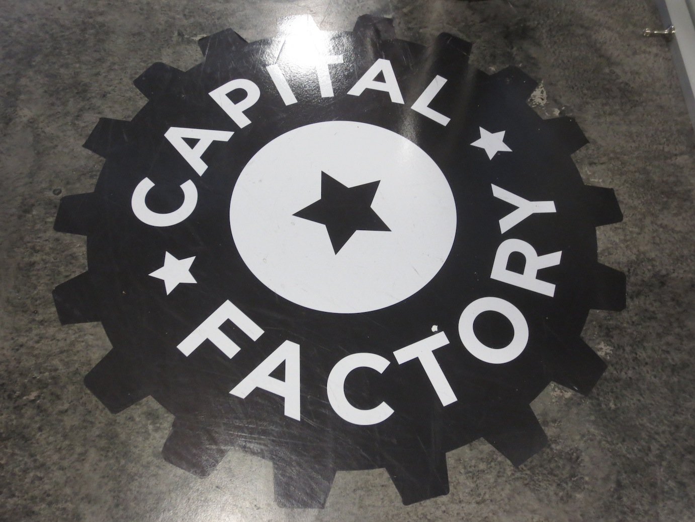 The logo for Capital Factory on the floor of their working space