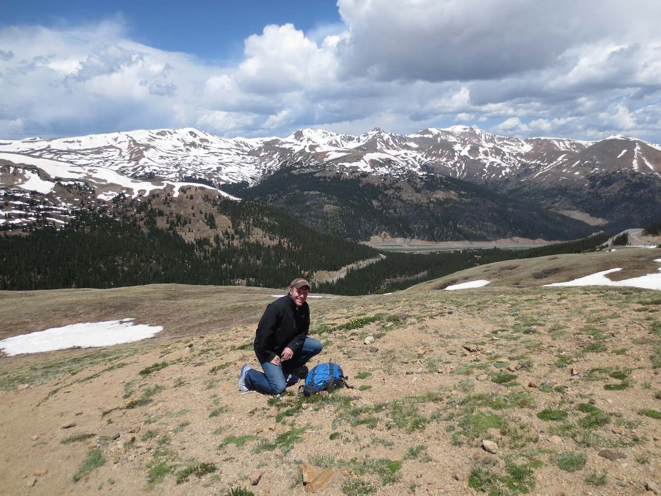Matt Makai kneeling in front of snow capped mountains in the distance.
