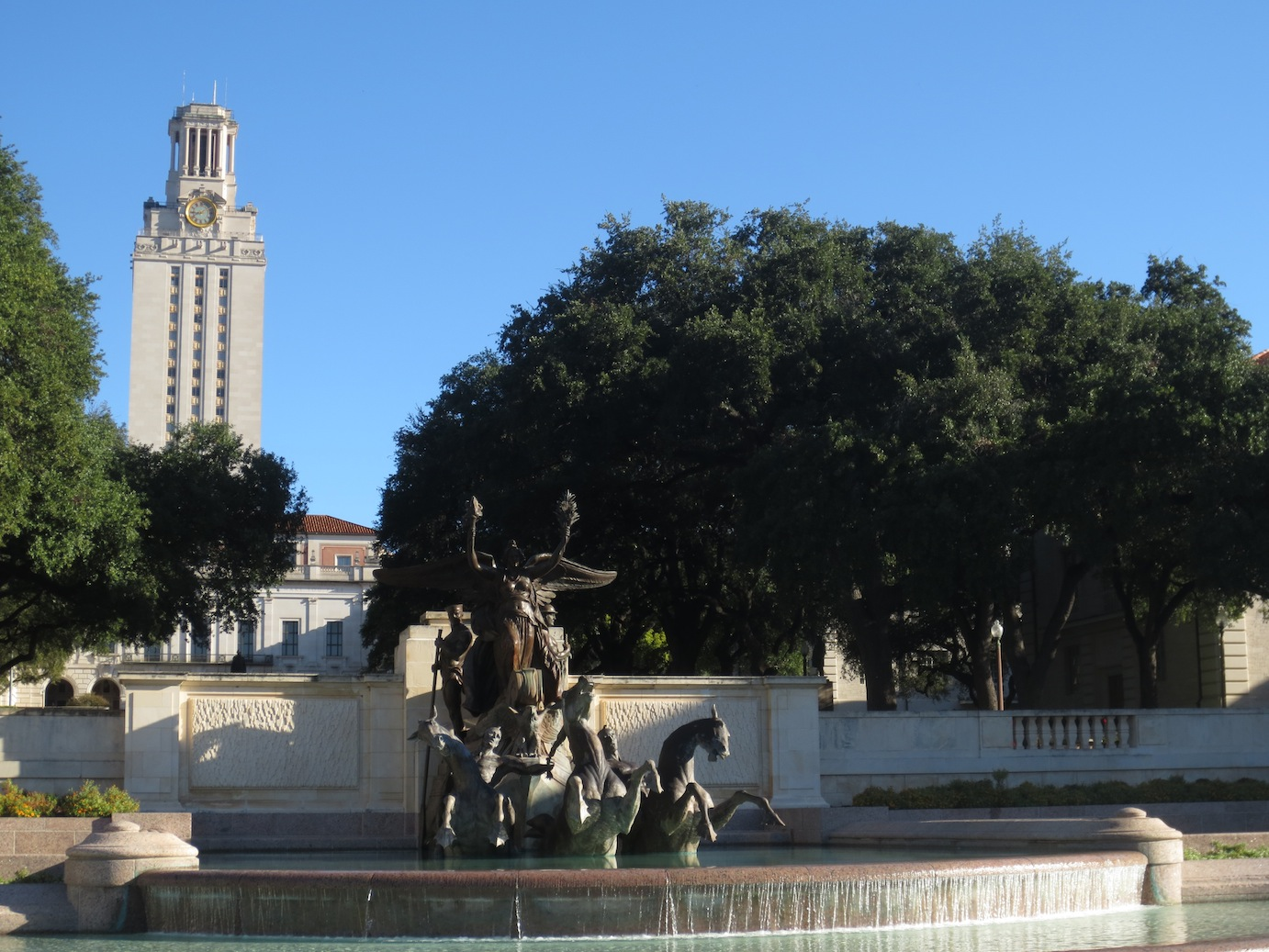 Fountain statue with the UT-Austin Bell Tower in the background.
